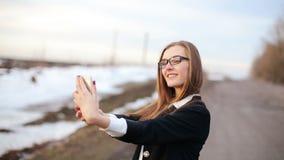 Het meisje strijkt het doen glad selfie gebruikend voor onder ogen ziende camera van smartphone stock video