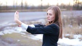 Het meisje strijkt het doen glad selfie gebruikend voor onder ogen ziende camera van smartphone stock footage