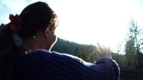 Het meisje in sweater bekijkt de zon door de hand Achter mening stock footage