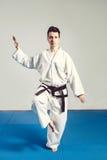 Het meisje, Taekwondo is krijgs opstookt indient vuisten, geconcentreerde, ernstige blik in de Studio op geïsoleerde achtergrond Royalty-vrije Stock Afbeeldingen