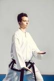 Het meisje, Taekwondo is krijgs opstookt indient vuisten, geconcentreerde, ernstige blik in de Studio op geïsoleerde achtergrond Stock Foto's