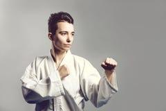 Het meisje, Taekwondo is krijgs opstookt indient vuisten, geconcentreerde, ernstige blik in de Studio op grijze geïsoleerde achte Royalty-vrije Stock Foto