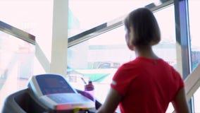 Het meisje tegen de achtergrond van een groot venster gaat op een renbaan stock videobeelden
