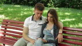 Het meisje toont aan haar vriend foto's in openlucht op een mobiele telefoon stock video