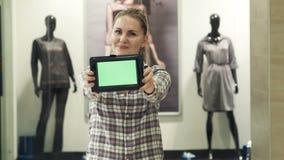 Het meisje toont de tablet met het groene scherm in wandelgalerij stock footage