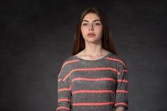 Het meisje toont droefheid tegen de donkere achtergrond Royalty-vrije Stock Afbeelding