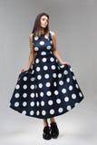Het meisje toont een kleding in erwten met grote boord aan royalty-vrije stock fotografie