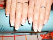 Het meisje toont een manicure, een apparaat om aan nagellak te drogen stock afbeeldingen