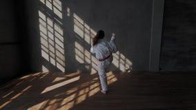 Het meisje toont een schopaanval in traditioneel taekwondo Originele vechtsporten van Zuid-Korea Gevechtshouding blootvoets stock footage