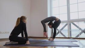 Het meisje toont een zuster haar flexibiliteit stock video