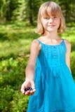 Het meisje toont geplukte bessen in een de zomer bos ondiepe nadruk royalty-vrije stock fotografie