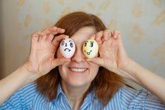 Het meisje toont geschilderde eieren voor Pasen met grappige gezichten stock afbeeldingen