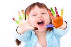 Het meisje toont haar gekleurde handen Stock Afbeeldingen