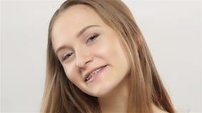 Het meisje toont haar glimlachsteunen wit Langzame Motie stock footage