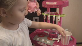 Het meisje toont haar speelgoedwerktuigen in de stuk speelgoed keuken stock footage