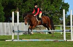 Het meisje toont het springen met poney Stock Foto
