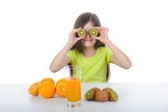 Het meisje toont kiwiplakken zittend bij de lijst Stock Afbeelding