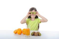 Het meisje toont kiwiplakken zittend bij de lijst Stock Foto's