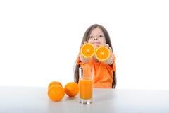 Het meisje toont oranje segmenten Royalty-vrije Stock Afbeeldingen