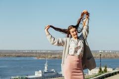 Het meisje toont tong met een open mond en heft het haar op royalty-vrije stock afbeelding