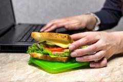 Het meisje treft voor diner voorbereidingen bij werk, die een sandwich, close-uplaptop het terugtrekken stock foto's