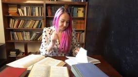 Het meisje treft voor het examen in de boeken van de bibliotheeklezing voorbereidingen stock video