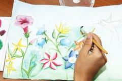 Het meisje trekt bloemen met waterverfverf op papier Stock Fotografie