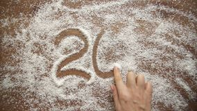 Het meisje trekt cijfers op kokosnotenvlokken Het meisje trekt op kokosnotenvlokken Nieuw jaar 2017 stock videobeelden