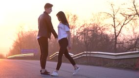 Het meisje trekt de kerel aan haar, het paar in liefde op de weg tijdens de dageraad, langzame motie stock footage