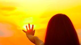 Het meisje trekt een hand aan de gouden zon stock video