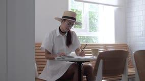 Het meisje trekt in een koffie stock videobeelden