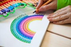 Het meisje trekt een regenboog Positieve tekening Kunsttherapie en relaxati stock afbeeldingen