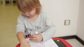 Het meisje trekt een rode teller op papier stock videobeelden