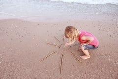 Het meisje trekt een zon in het zand op het strand Royalty-vrije Stock Afbeeldingen