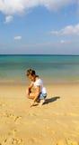 Het meisje trekt in het zand op het strand Stock Foto