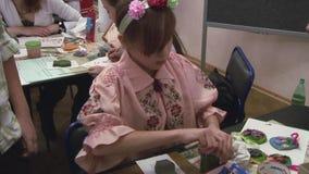 Het meisje trekt met de hand gemaakte vaas van klei bij lijst door borstel in groene kleur festival verwezenlijking hobby stock footage