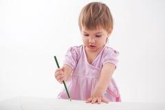 Het meisje trekt met kleurpotloden Stock Foto