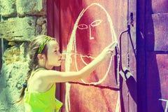 Het meisje trekt met krijt Stock Foto's