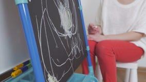 Het meisje trekt met krijt op het bord in het kinderdagverblijf Het mamma zit naast haar en bewondert het kind stock videobeelden