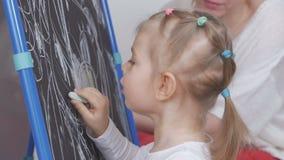 Het meisje trekt met krijt op het bord in het kinderdagverblijf Het mamma zit naast haar en bewondert het kind stock video