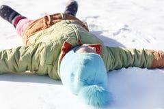 het meisje trekt op de sneeuwengel Ondiepe Diepte van Gebied stock fotografie