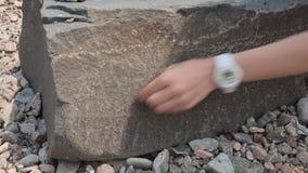 Het meisje trekt op een rots stock video