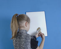 Het meisje trekt op een witte plastic raad stock foto's