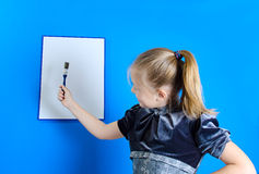 Het meisje trekt op een witte plastic raad royalty-vrije stock afbeelding
