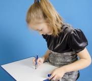 Het meisje trekt op een witte plastic raad royalty-vrije stock afbeeldingen