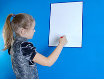 Het meisje trekt op een witte plastic raad stock foto