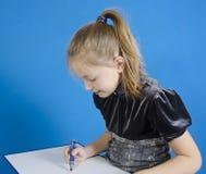 Het meisje trekt op een witte plastic raad royalty-vrije stock foto's