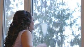Het meisje trekt op het hart op het venster stock video