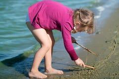 Het meisje trekt op het zand Stock Fotografie