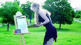 Het meisje trekt op pleinlucht op groen gras in park stock video